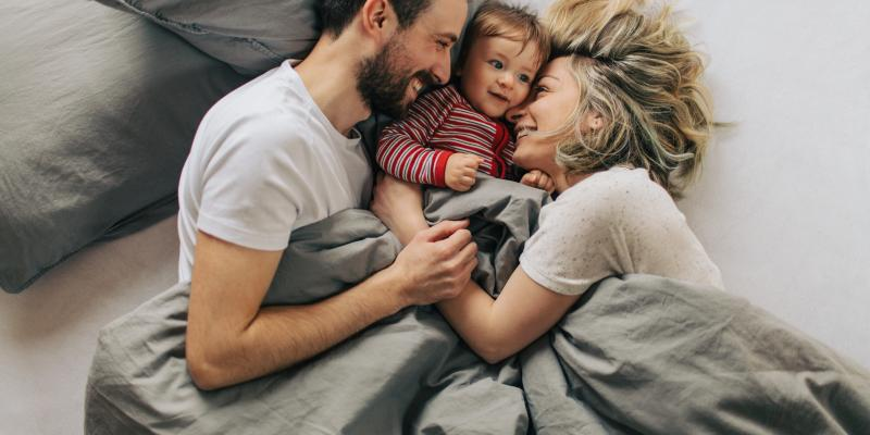 mom, dad, and child laying in bed cuddling.