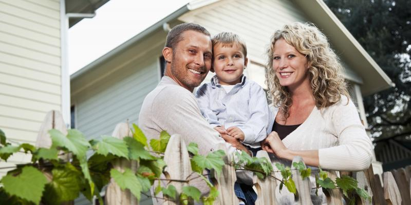 family of three smiling at camera in garden outside of their house